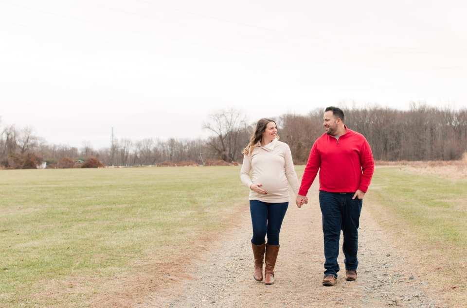 Mom and Dad to be holding hands, lovingly looking at each other while walking through a park on a winters day in New Jersey Maternity Photos