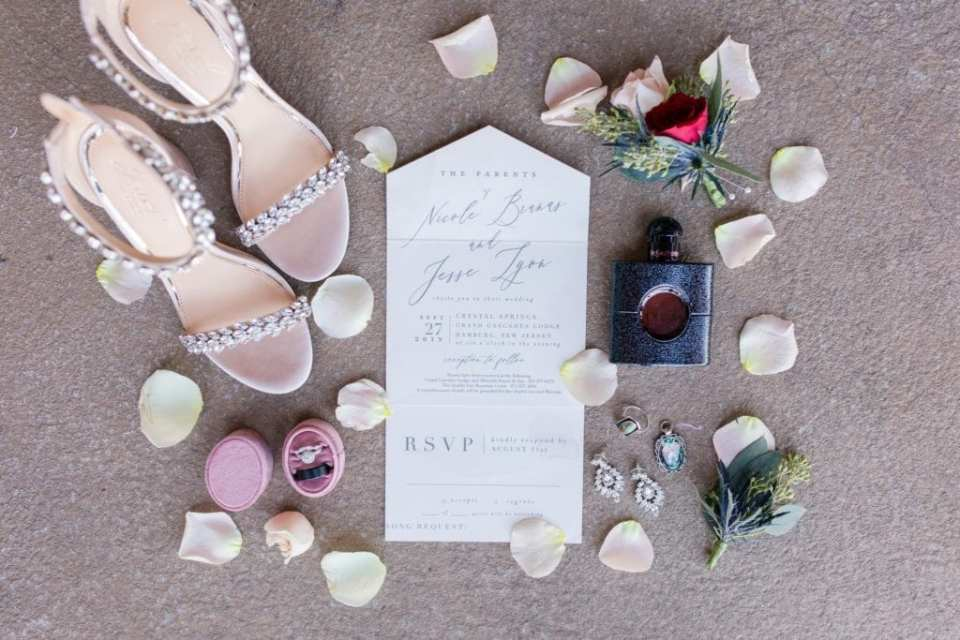 Wedding details: invitation, brides shoes, rings, jewelry, cologne and blush rose petals