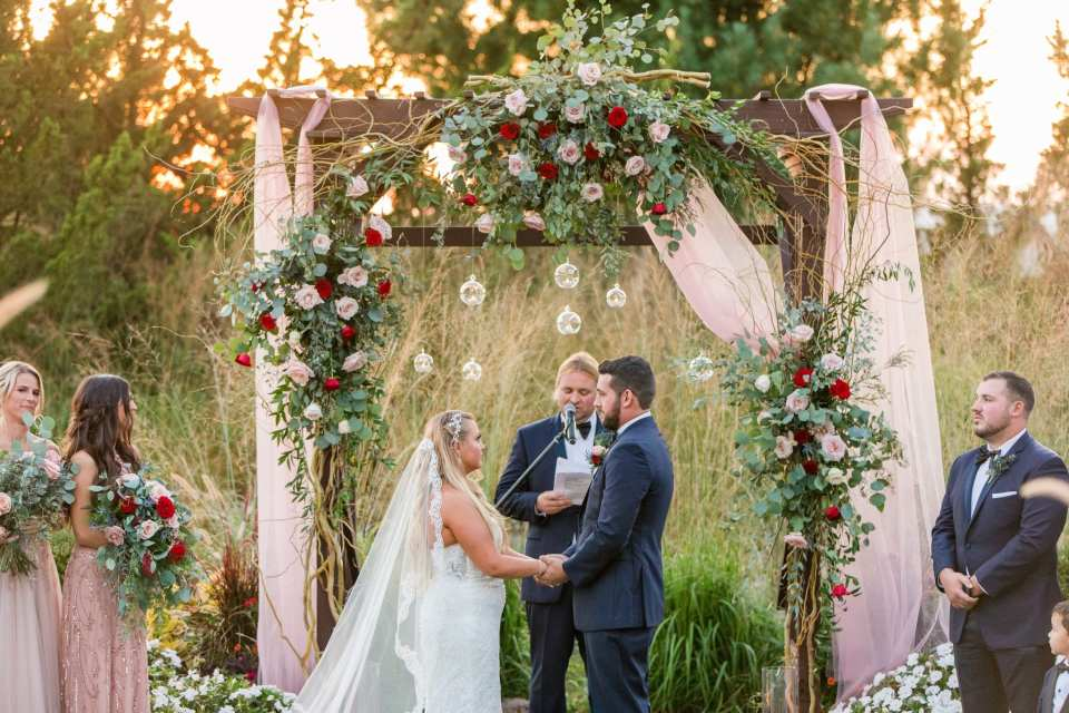 The bride and groom during their outdoor ceremony under a dark wood trellis decorated with pink fabric, greenery, blush and red roses and clear hanging candleholders by Added Touch Florist at the Grand Cascades Lodge at Crystal Springs Resort