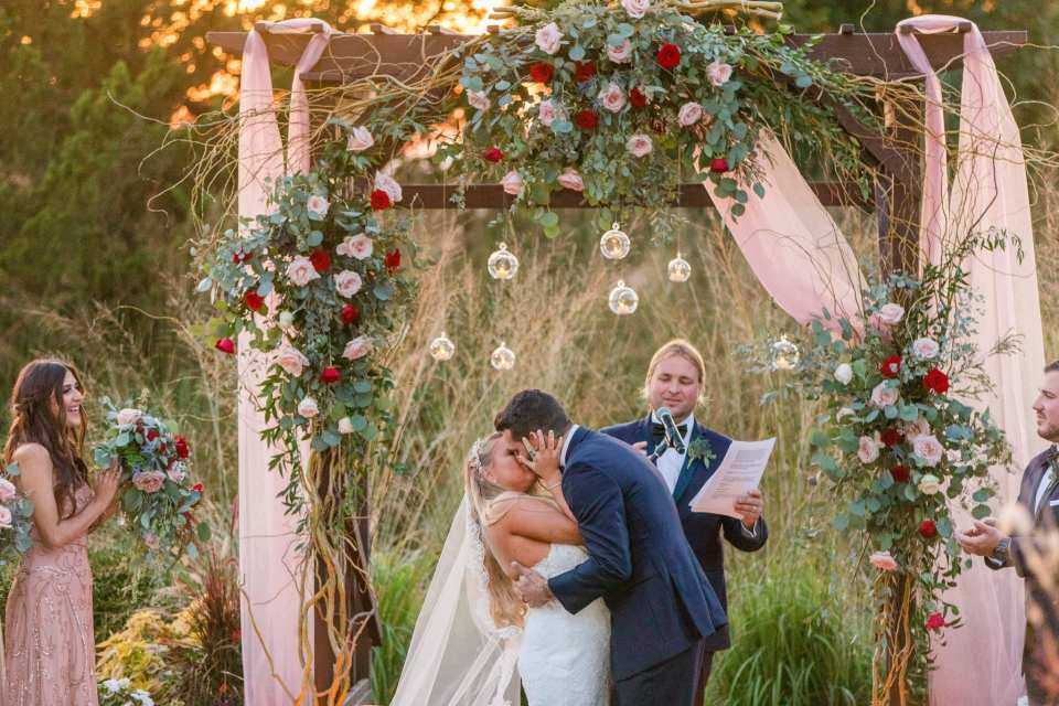 The bride and groom share their first kiss as husband and wife in an outdoor ceremony under a dark wood trellis decorated with pink fabric, greenery, blush and red roses and clear hanging candleholders by Added Touch Florist at the Grand Cascades Lodge at Crystal Springs Resort