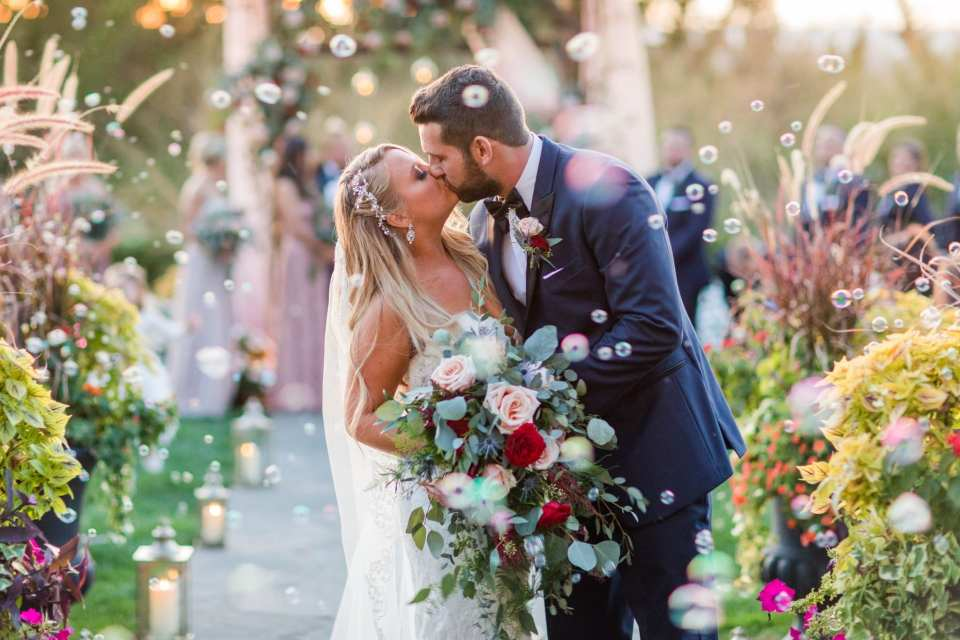 The bride and groom share a kiss at the end of the aisle after being pronounced husband and wife in the midst of waves of bubbles