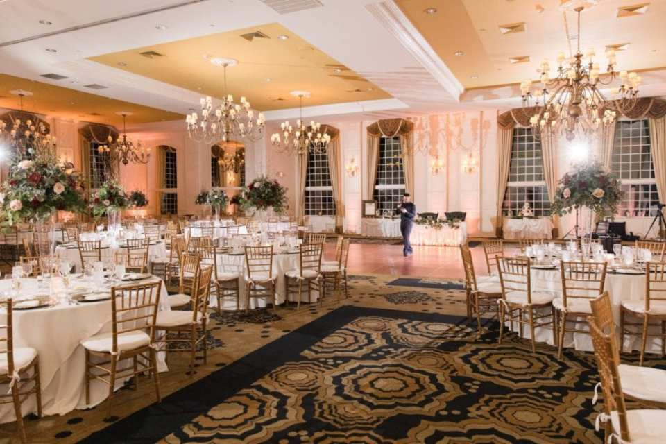 Ballroom at the Grand Cascades Lodge at Crystal Springs Resort decorated with classic gold chivari chairs, ivoryy table linens, and tall floral arrangements with an abundance of greenery and roses in blush and red by Added Touch Florist