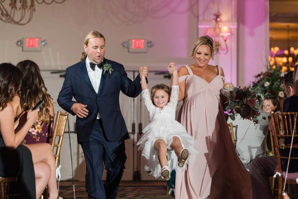 Members of the wedding party make their entrance into the wedding reception. His tuxedo by Chazmatazz, her light pink gown from Bella Bridesmaids