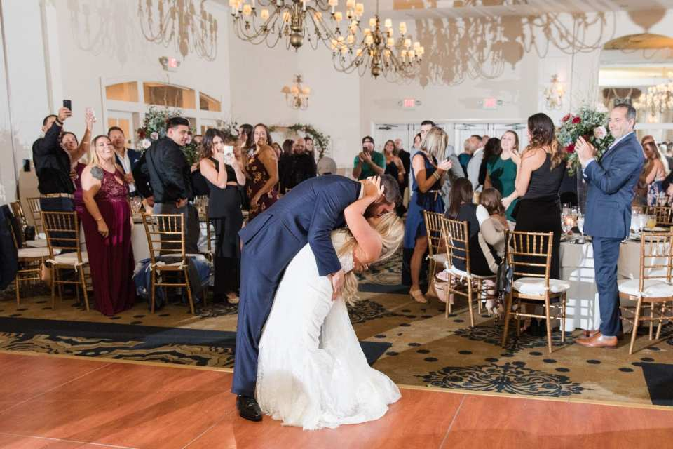 The groom dips his bride for a kiss after making their grand entrance into their wedding reception at the Grand Cascades Lodge at the Crystal Springs Resort