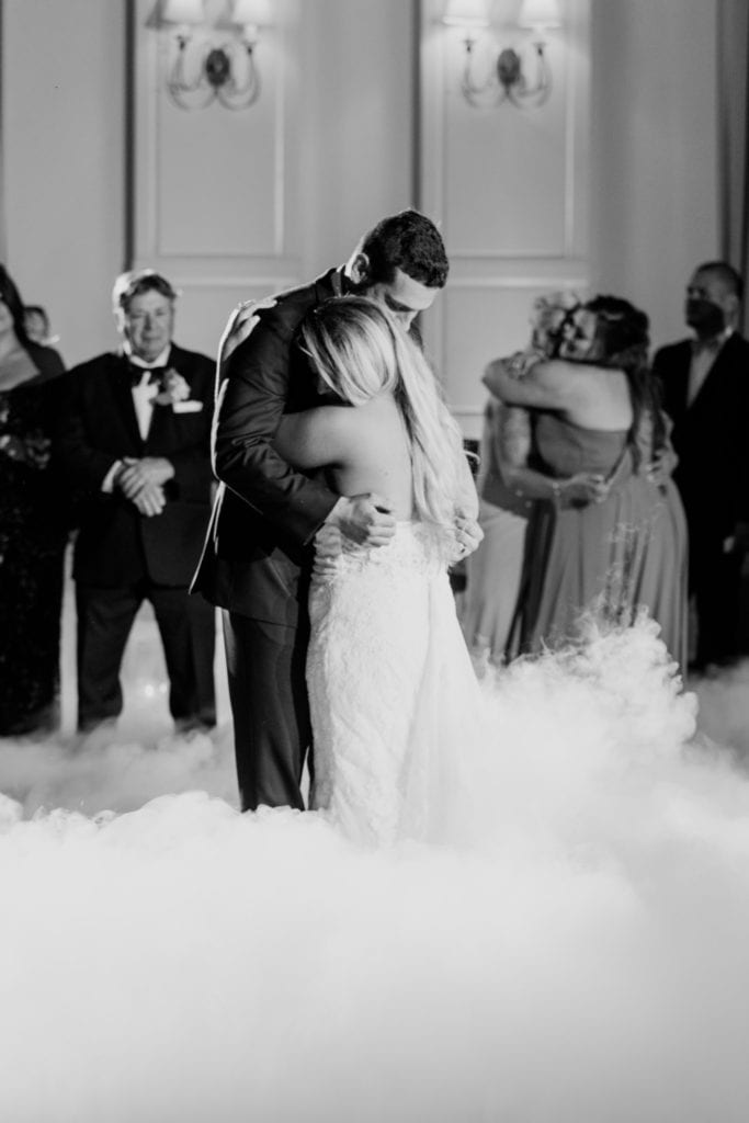 Black and white photo of the bride and groom having their first dance, surrounded by smoke effects by DJ Tony Gia