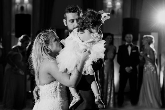Black and white photo of the bride and groom sharing a dance with their small daughter