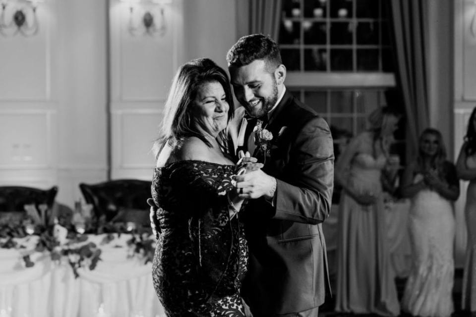 Black and white photo of the groom dancing with his mother. The bride watches from a distance.