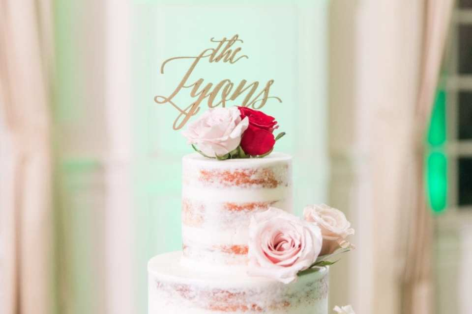 Custom gold cake topper on top of semi-naked multi-tiered wedding cake decorated with roses in shades of blush and red
