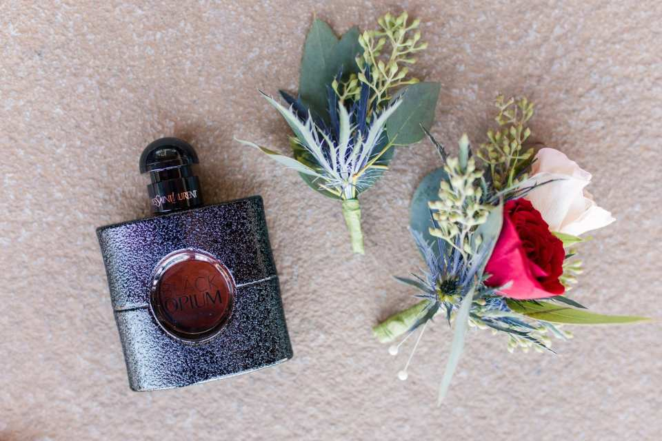 Grooms details: cologne and boutonnieres of greens and greens with blush and red roses