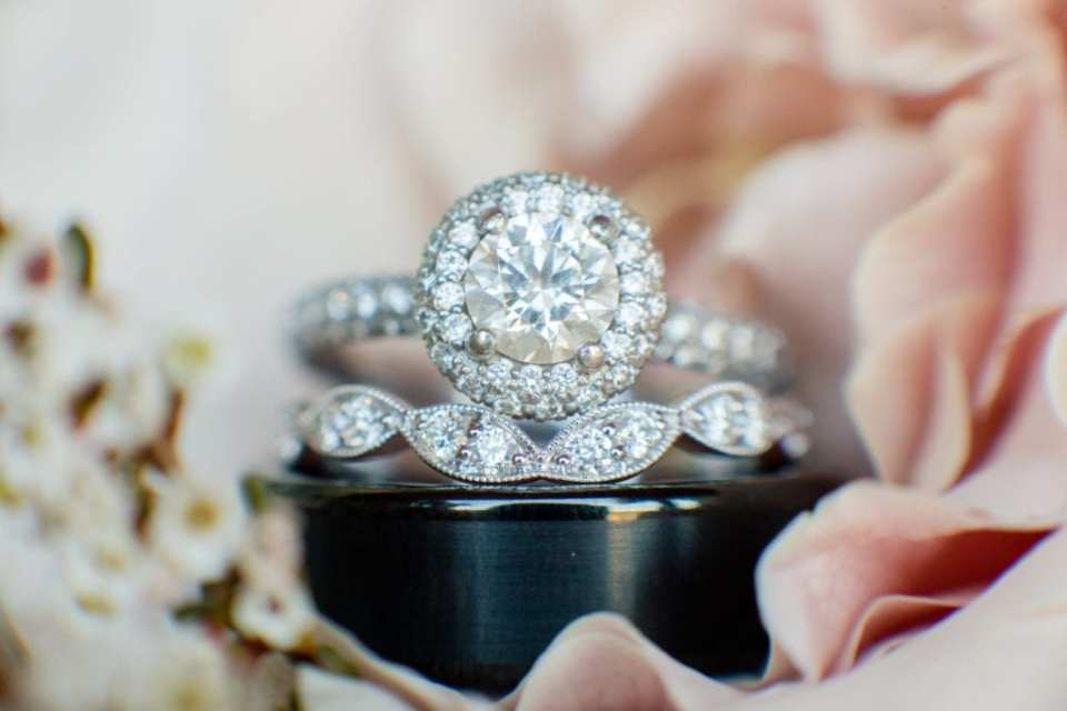 The brides round diamond with diamond halo engagement ring on display with her antique diamond wedding band