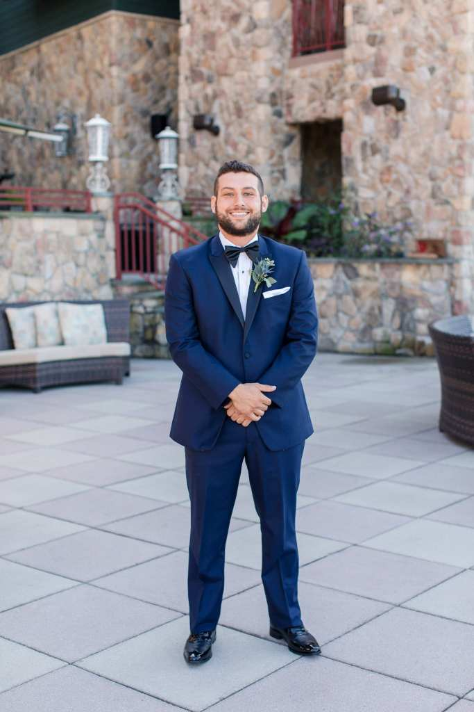 Full length photo of the groom in his navy blue tuxedo by Chazmatazz
