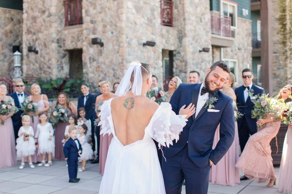 The groom laughs while checking out his groomsman in a wedding gown during a faux first look as the bridal party laughs and watches in the background