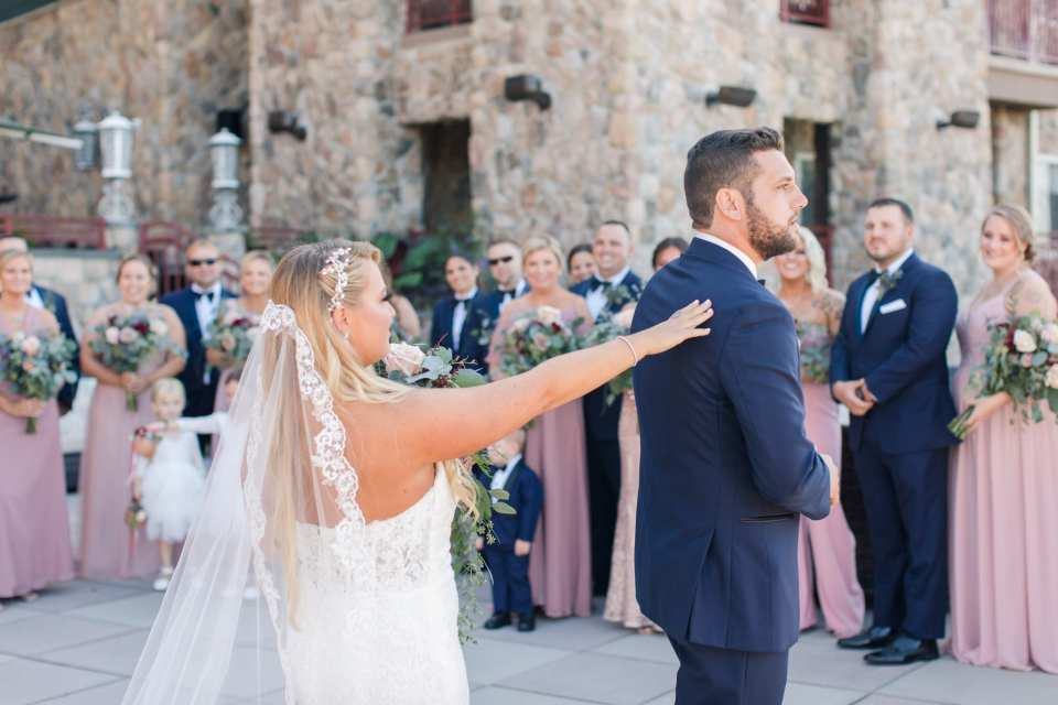 The bride touching the back of her groom during their first look as the entire wedding party looks on
