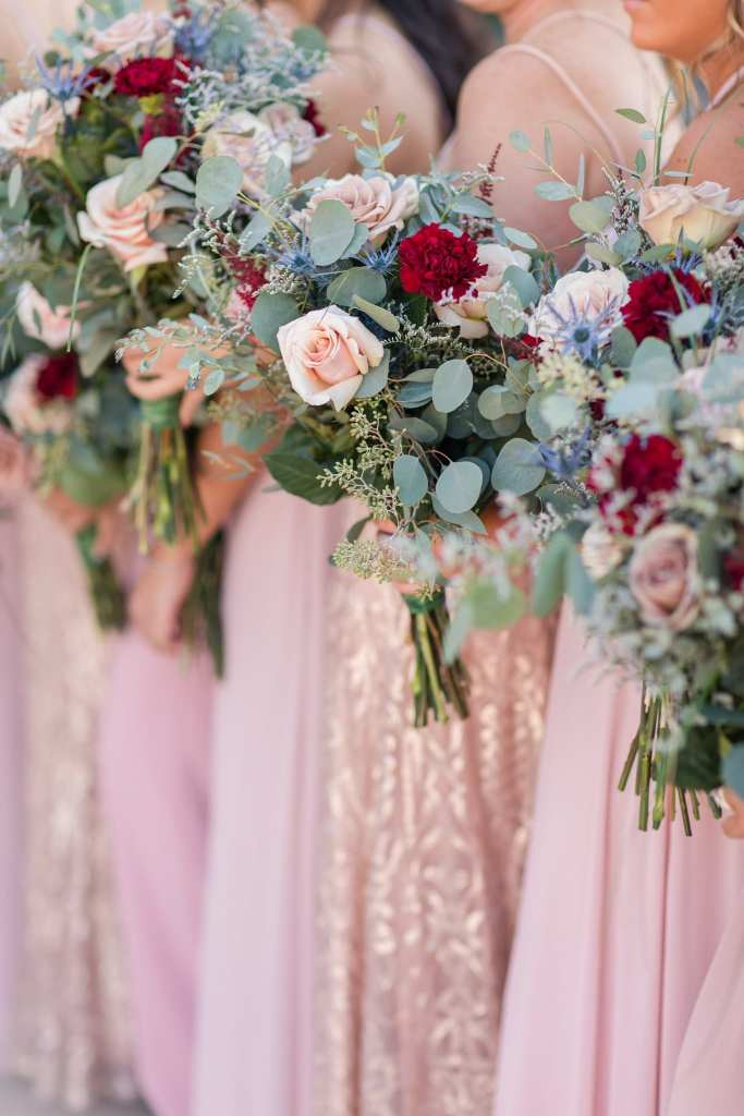 Focus on the bridal party bouquets of red and blush florals, with added greenery by Added Touch Florist