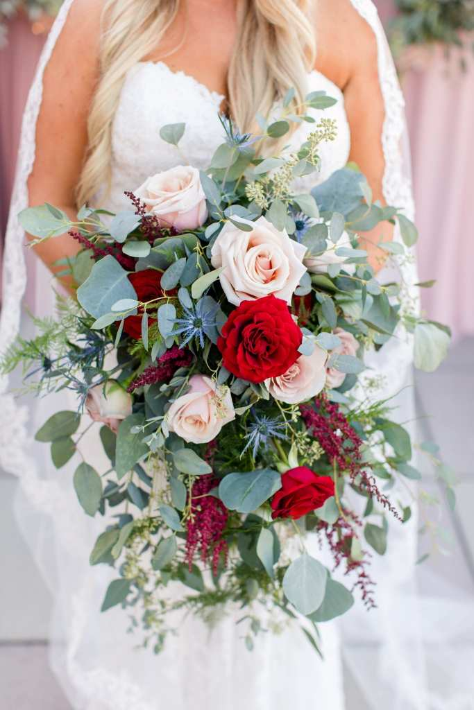 Focus on the bridal bouquet of blush and red florals surround by various greenery by Added Touch Florist