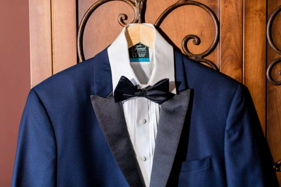 A close up of the grooms navy and black tuxedo by Chazmatazz on display