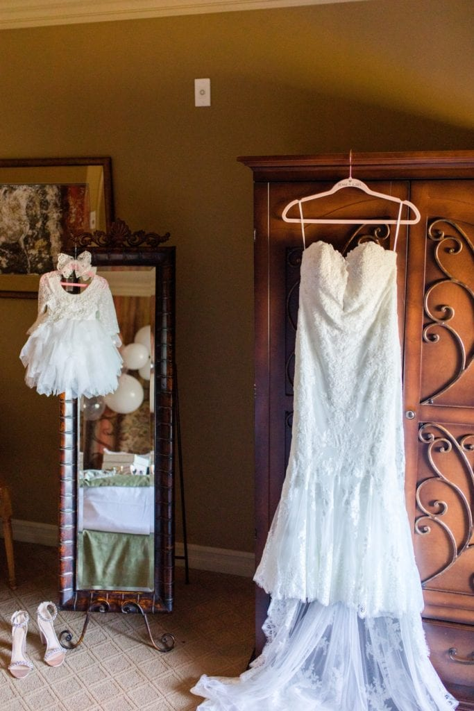 The brides Pronovias white lace and tulle gown on display along with her daughters coordinating white lace and tulle dress