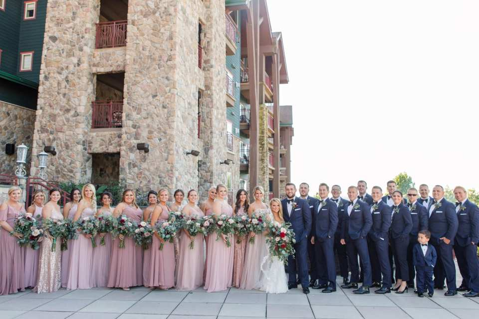 Entire wedding party. The bridal party in gowns in shades of pink from Bella Bridesmaids, the groomspeople in navy blue and black tuxedos by Chazmatazz.