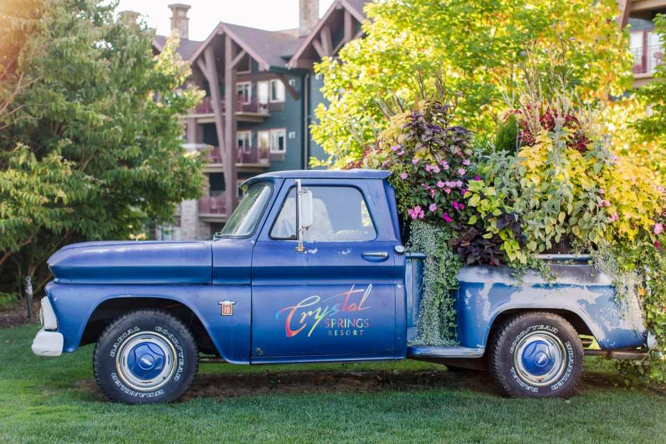Antique blue truck with bed of truck filled with plants, outside the Grand Cascades Lodge at Crystal Springs Resort