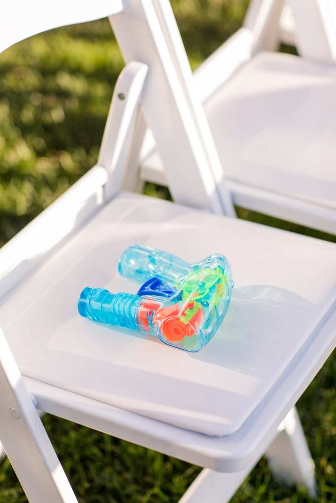 Bubble gun on white wooden folding chair for blowing bubbles when the new mr and mrs make their way down the aisle