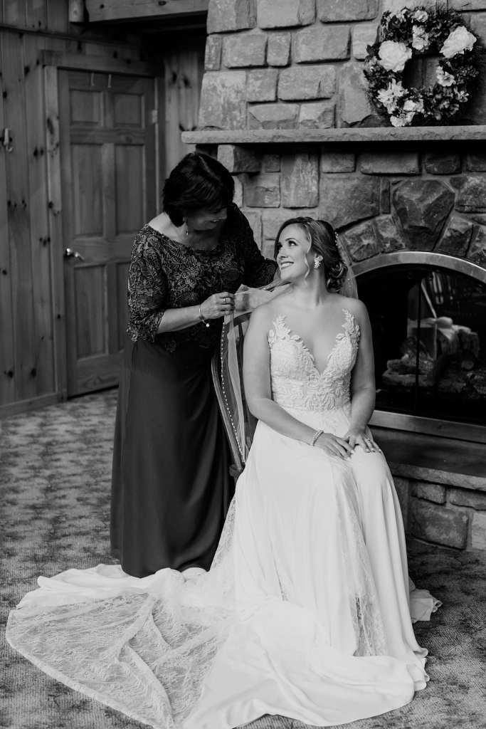 Black and white photo of the bride sitting in front of a fireplace gazing up at her mother