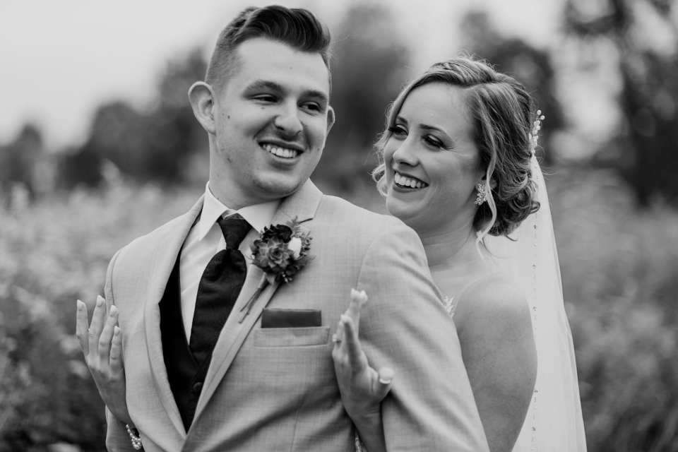 Black and white photo of the bride and groom in a fun photo, bride behind