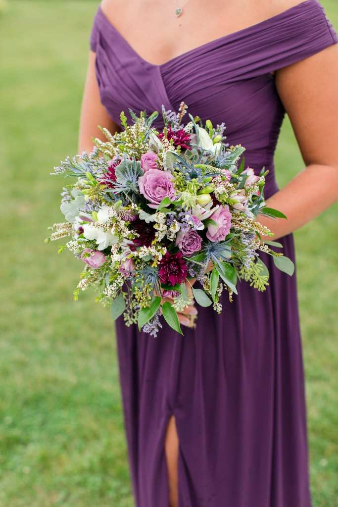3/4 photo of a bridemaid in a purple off the shoulder gown by David's Bridal holding a bouquet of wildflowers by Ross Plants & Flowers