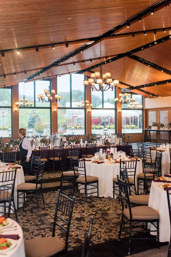 Wide angle photo of the ballroom at Blue Mountain Resort with different shaped tables with white linens and small floral arrangements and black chivari chairs in these Blue Mountain Resort Wedding photos