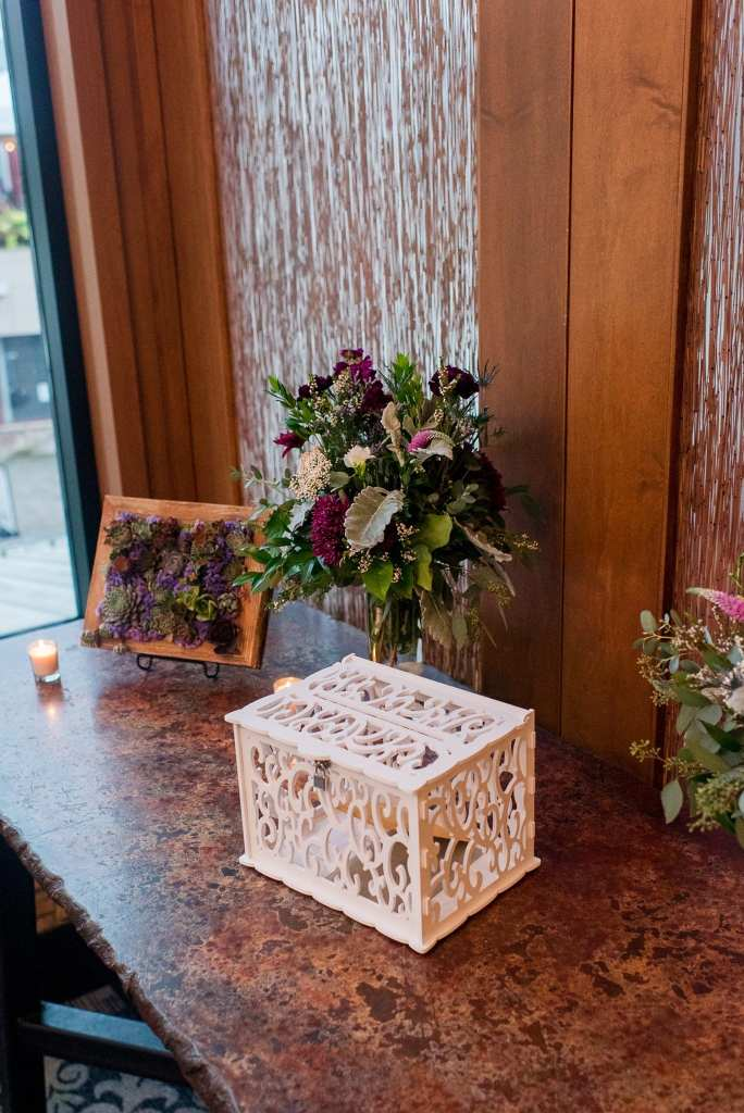 Wedding details: a white handcarved card box on display with wildflower arrangements and succulent arrangements