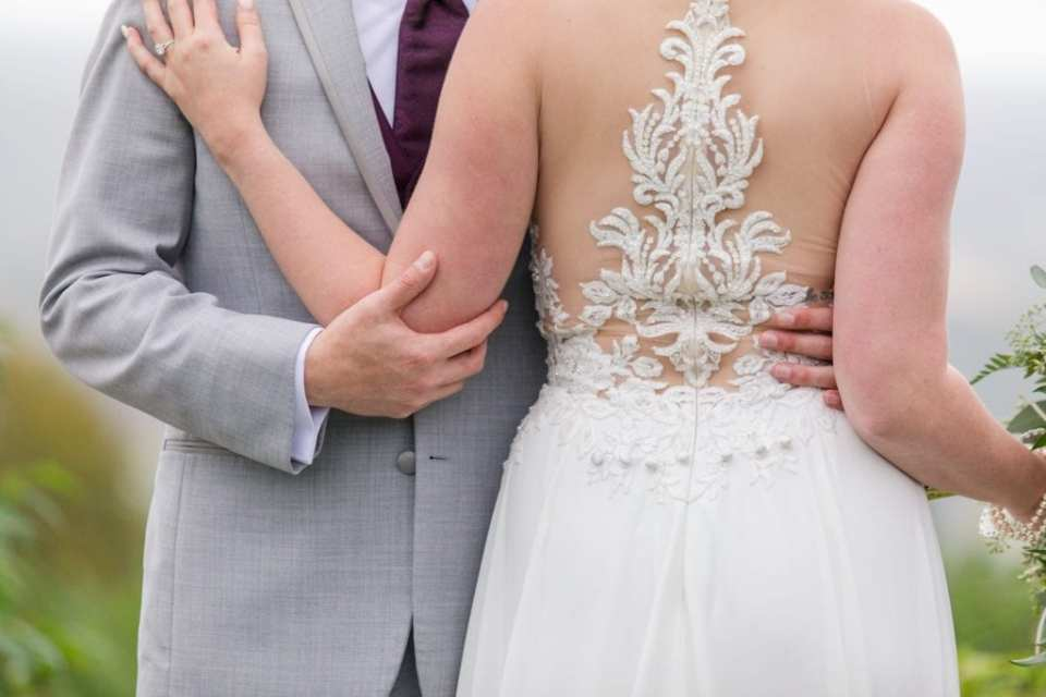 Close up of the back of the brides Allure bridal gown while standing with her groom in his light grey suit