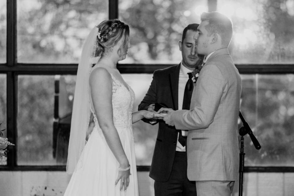 Black and white image of the bride and groom exchanging rings