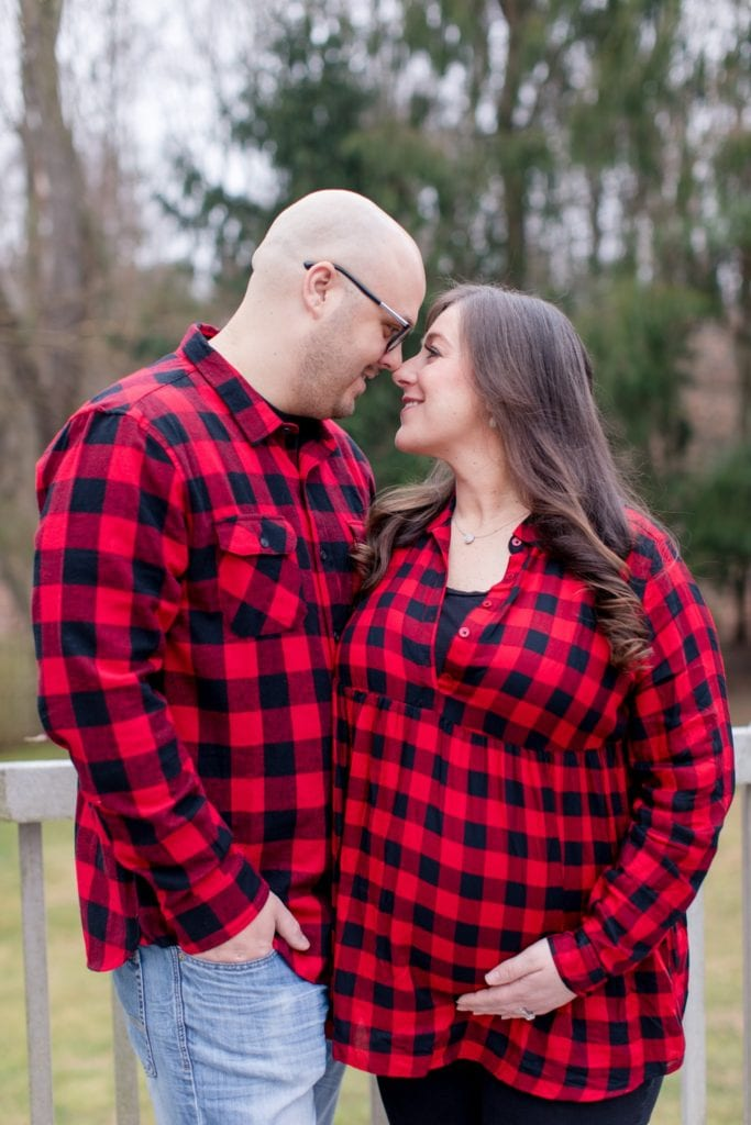 Mom and Dad to be, nose to nose outside, in coordinating red flannel tops