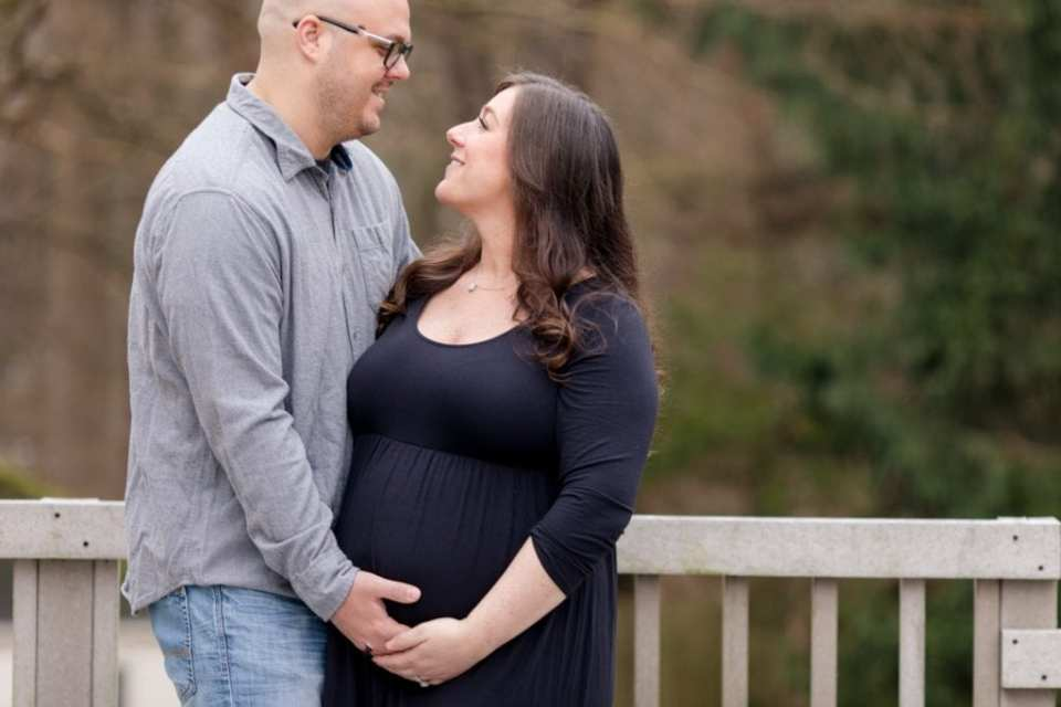 Mom to be in traditional black maternity gown in her husbands arms outdoors
