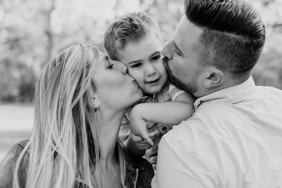 Black and white photo of Mom and Dad kissing the cheeks of their small son. Allaire state park family photos