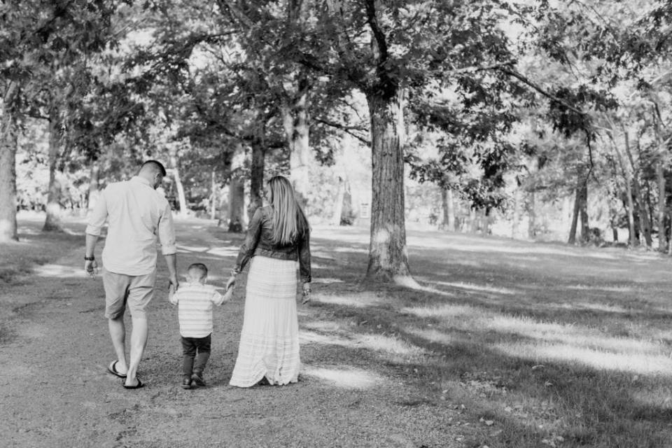 Wide angle black and white photo of family of three, all holding hands, walking away from camera amongst trees