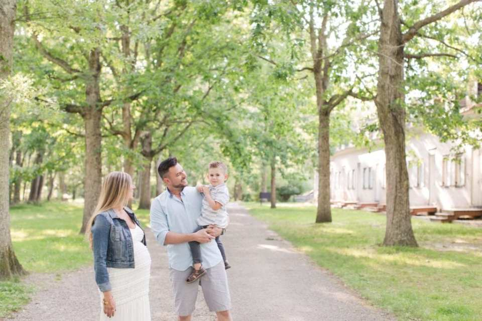 Candid wide angle photo of family of three enjoying one another's company outside amongst trees