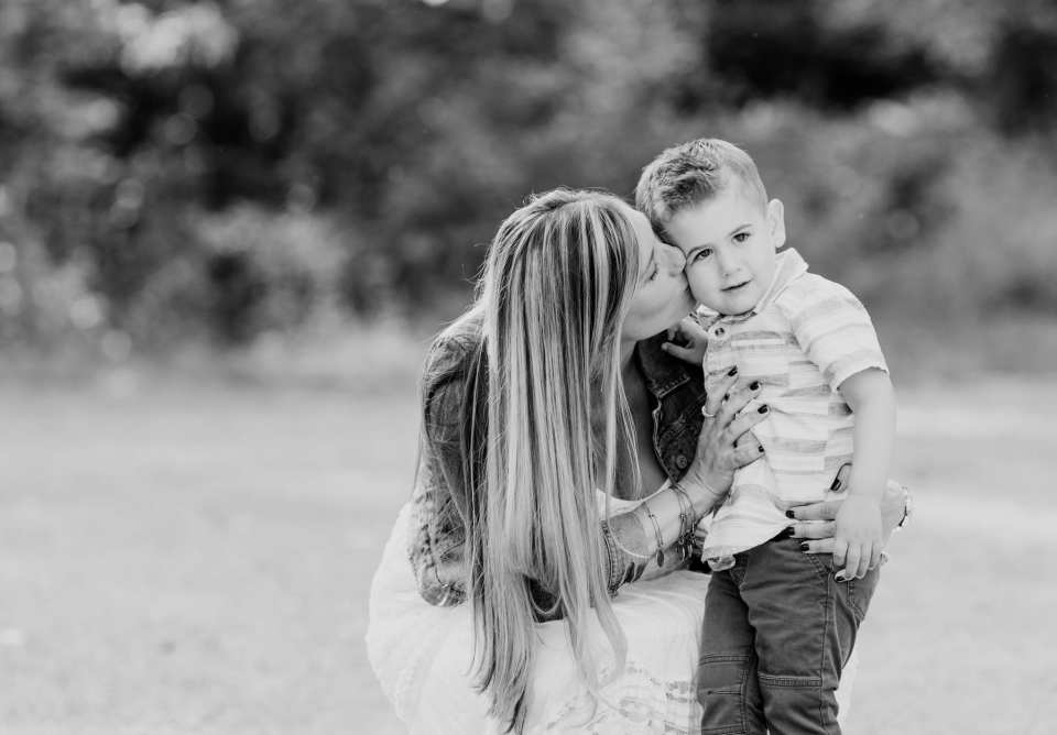 Black and white of Mom kneeling down to level of small son, kissing his cheek
