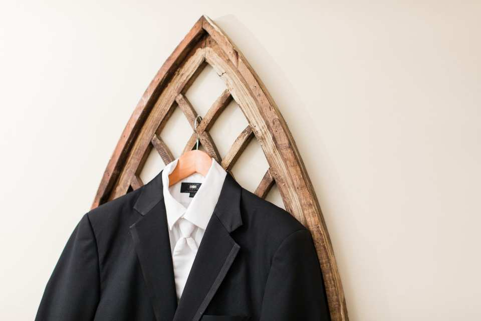 Groom's Men's Wearhouse tuxedo displayed on a unique hanging
