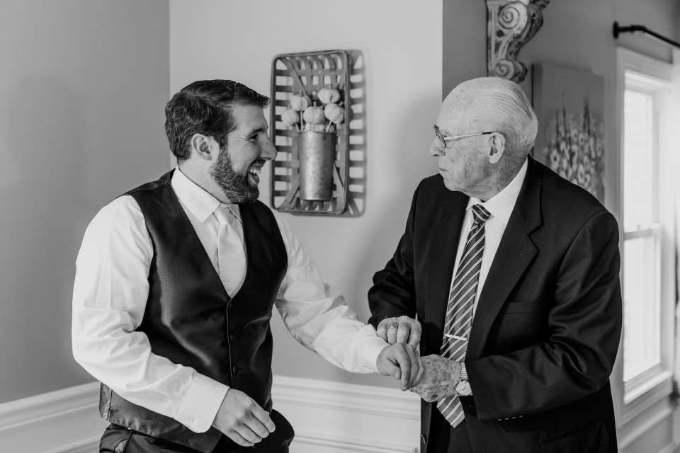 Black and white candid of the groom and his father helping him with his cufflinks