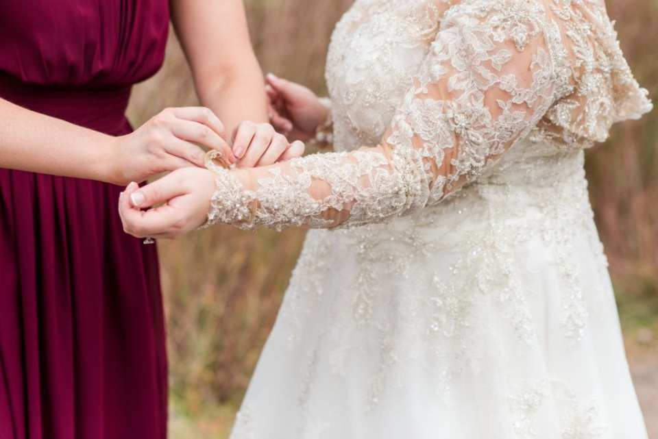 Close up of the maid of honor in a dark red gown assisting the bride with the lace details of her Justin Alexander bridal gown