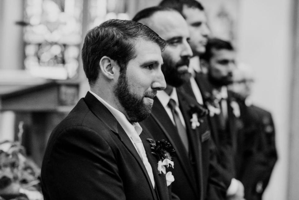 Black and white candid photo of the groom watching his bride walk down the aisle towards him
