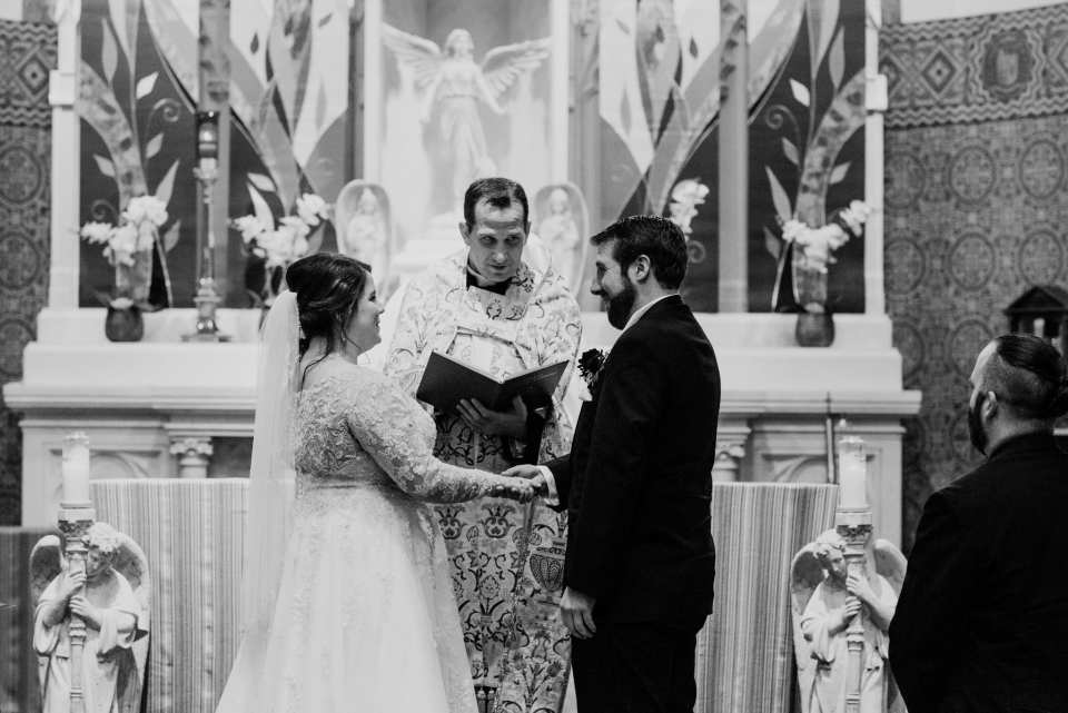 Black and white photo capturing the bride and groom exchanging vows with one another