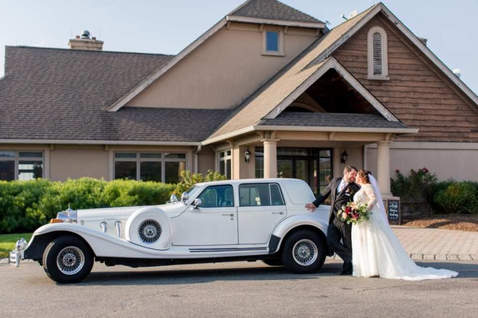 Portrait of bride and groom, nose to nose, in front of their antique automobile transportation by Moonlight Limo Service in front of the Ballyowen Golf Course Clubhouse