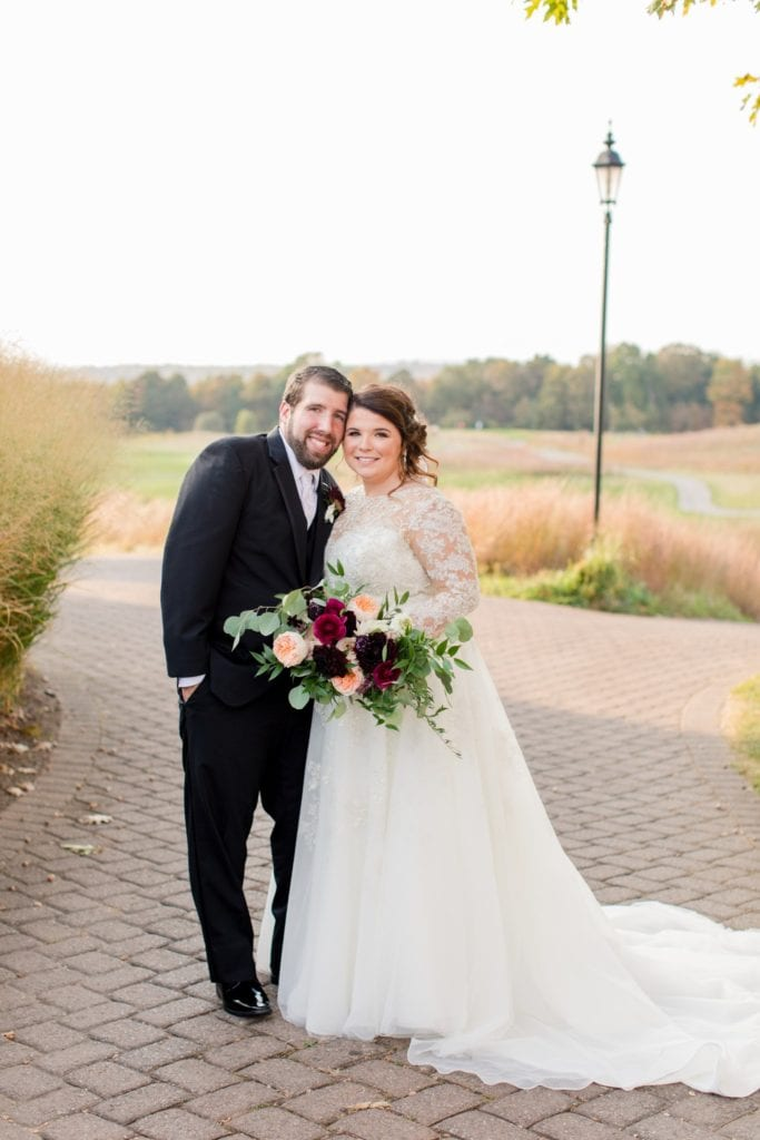 Formal portrait of the bride and groom, her bridal bouquet by Whisper and Brook Flower Co. prominently displayed Ballyowen Golf Course in background