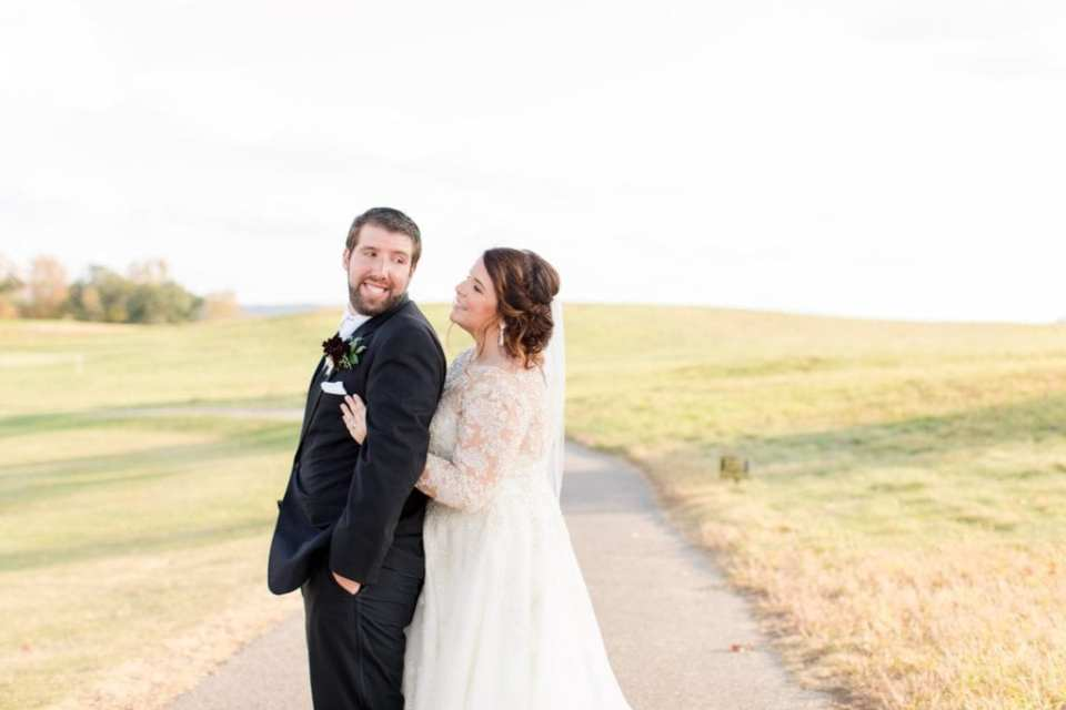 Wide angle portrait of bride and groom, she standing behind him, he looking back over his shoulder at his bride Ballyowen Golf Course in background