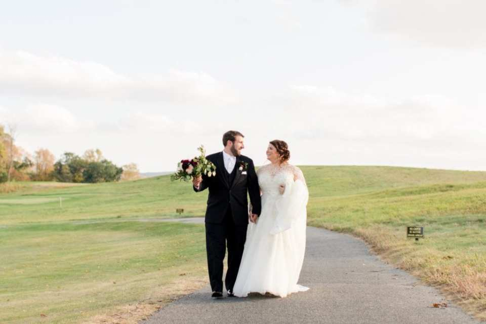 The bride in her Justin Alexander gown, train over her arm, walking hand in hand with her groom, in a black Mens Wearhouse tuxedo with Ballsyowen Golf Course in background