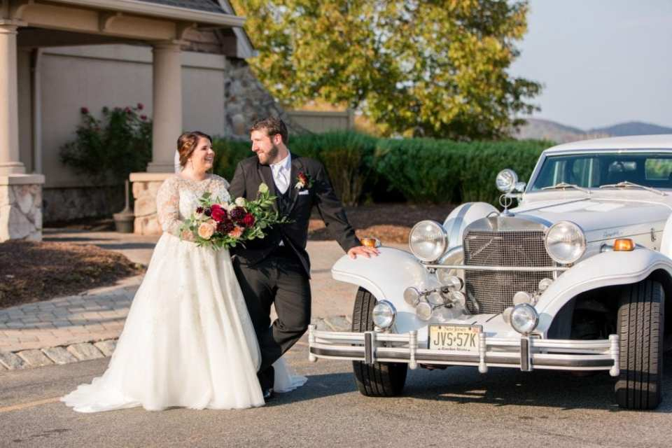Portrait of bride and groom in front of their antique automobile transportation by Moonlight Limo Service in front of the Ballyowen Golf Course Clubhouse