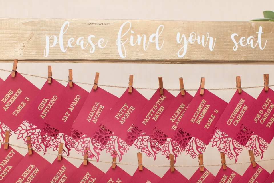 Hanging seating arrangement with handmade dark red and gold escort cards created by the bride