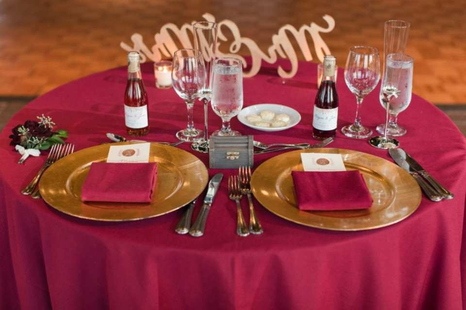 Close up of the sweetheart table in dark red linens with gold charger accents