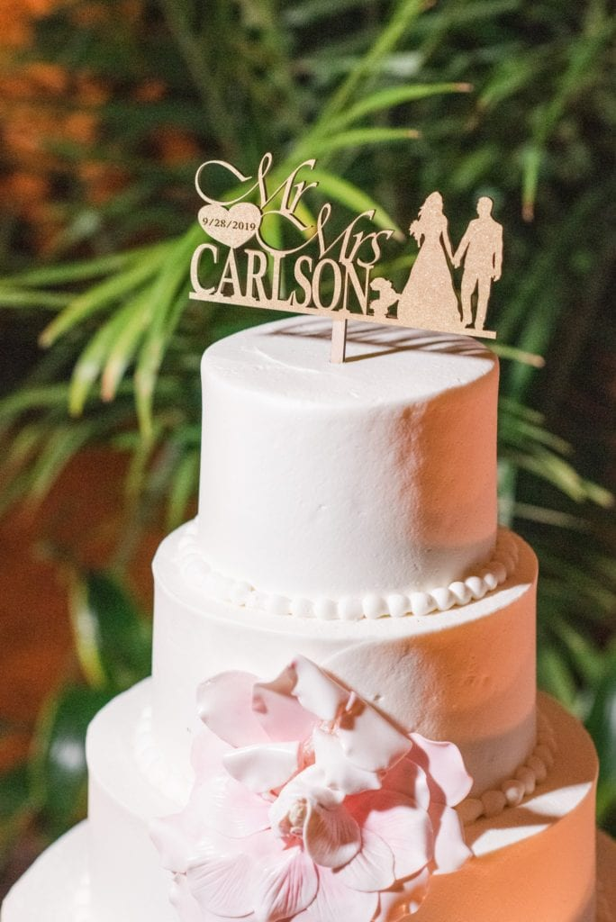 Close up of 4 tier white wedding cake with blush floral accents by Cafe Pierrot and custom gold cake topper